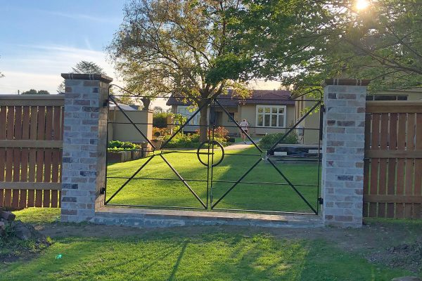 Gateway is constructed using recycled brick gate columns and customised iron gates